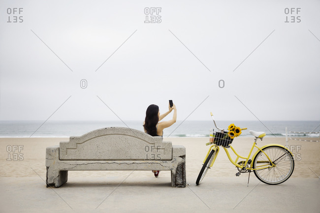 A woman sits on a bench and takes a selfie
