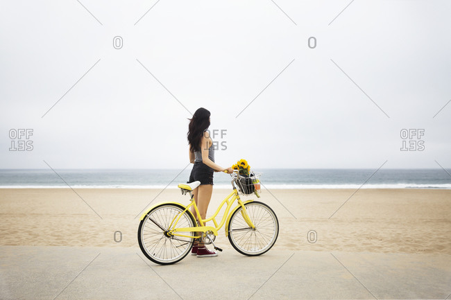 A woman stands by the beach with her bike