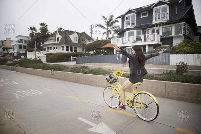 A woman rides a bike with no hands
