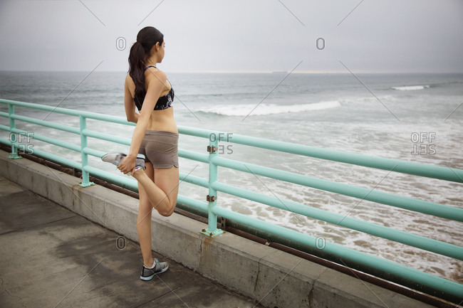 A woman stretches by the ocean