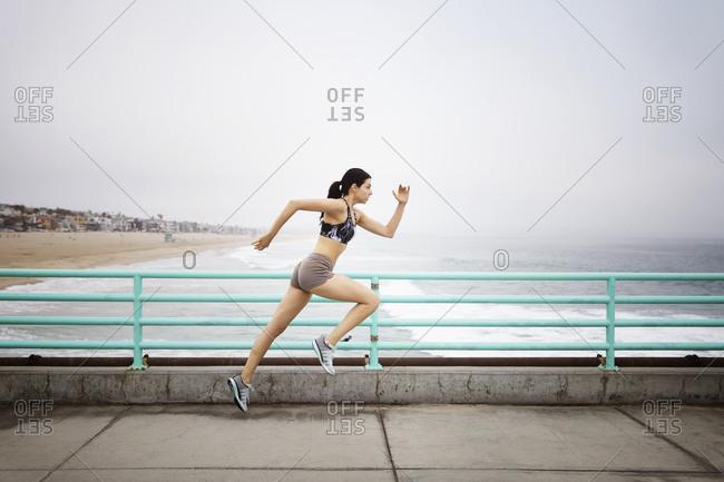 A woman sprints down a pier