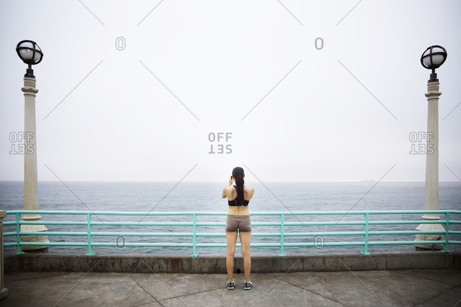 A jogger stops to take a photograph of the ocean