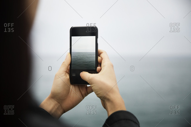 A woman takes a picture of the ocean