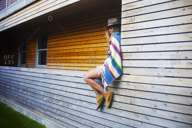 A young woman sits on the wall of a house wrapped in a serape