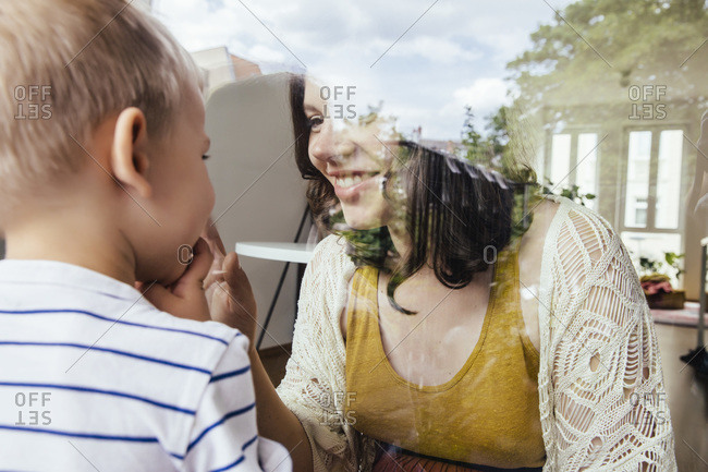 Mother and son making contact through a window