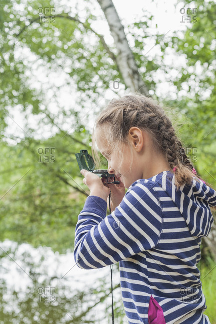 Girl looking through compass
