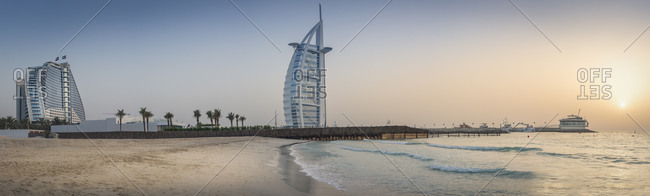 Dubai, UAE - July 10, 2015: Sunset at Jumeirah Beach with Burj al Arab and Jumeirah Beach Hotel