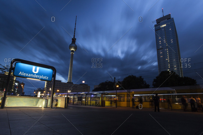 Lighted underground station and tramway in front of television tower at Alexanderplatz, Berlin