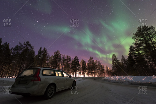 Car on Arctic road and Northern Lights