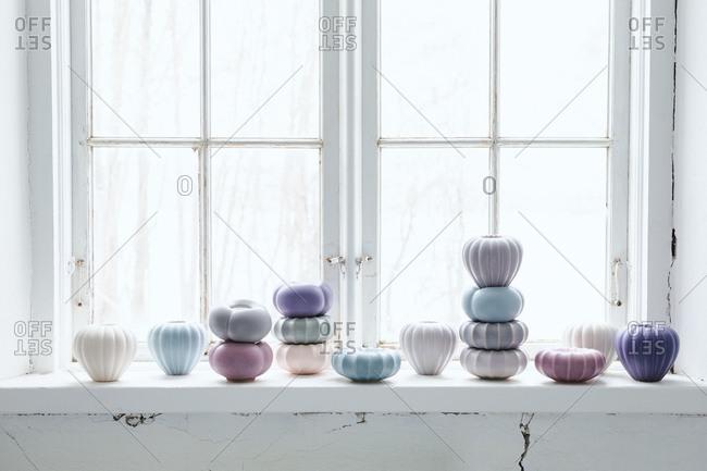 Tiny pastel ceramic candle jars and vases on a windowsill