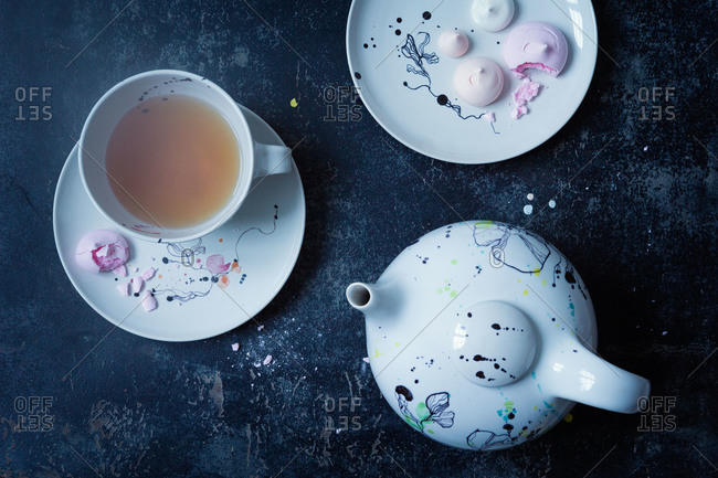 Tea and meringue cookies served on painted ceramic dishware