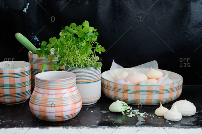 Striped ceramic dishware filled with fresh herbs and meringues