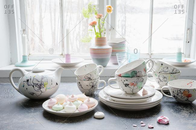 A ceramic tea set next to a window
