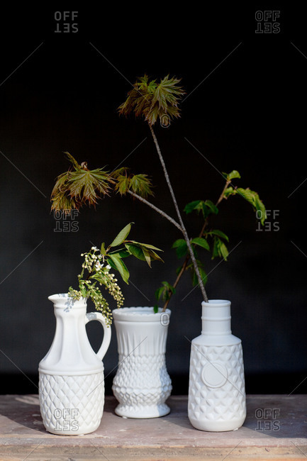 Three white vases on a wood table