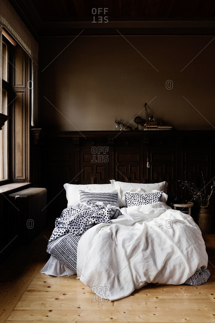 A dark wood bedroom with bright white linens