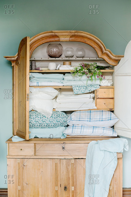 An armoire filled with blue and white linens