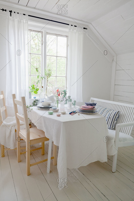 A table with a white tablecloth in a Swedish country kitchen