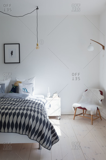 A white bedroom with a pendant light bulb in a Swedish home