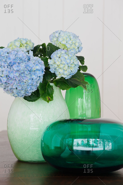 Blue hydrangeas in a green vase in a home in Sweden