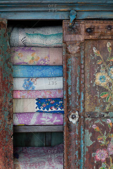 Vintage quilts in a worn armoire in a home in Sweden
