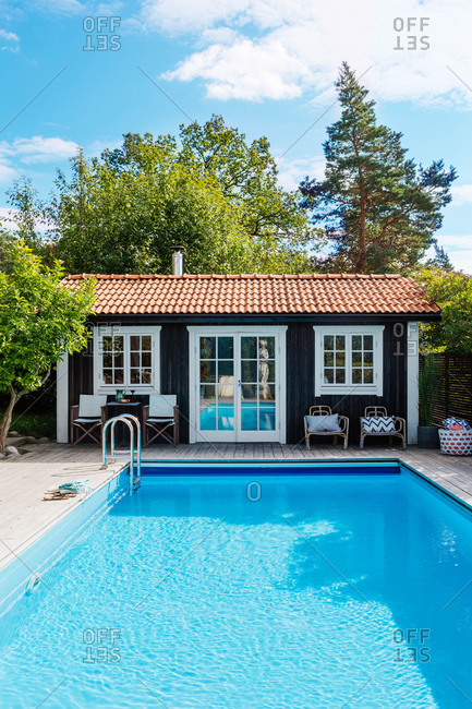 A dark wood pool house next to a blue pool in Sweden