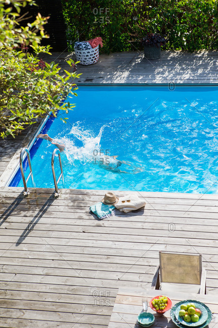A man dives into a blue pool in a backyard in Sweden