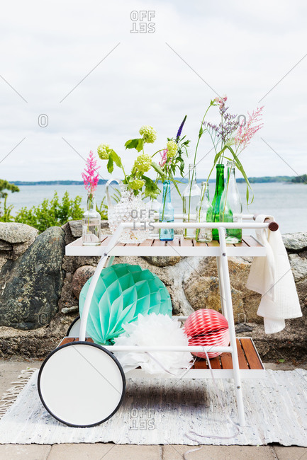 A pushcart covered in glass bottles by a lake in Sweden