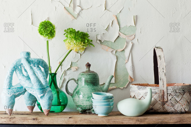 Vases and dishware in front of peeling paint