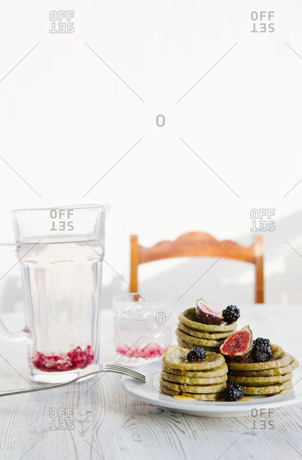A stack of small pancakes with fruit