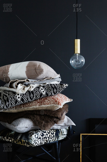 A stack of throw pillows in a black room