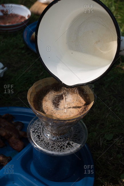 Pouring water into coffee dripper at campsite