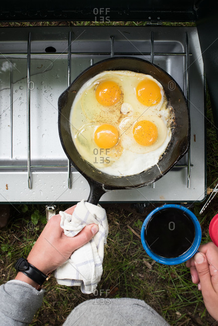 Woman cooking eggs on a camp stove
