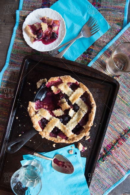 Blueberry plum pie with a slice on a plate