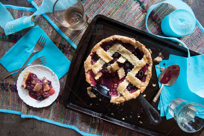 Blueberry plum pie in pan and slice on plate