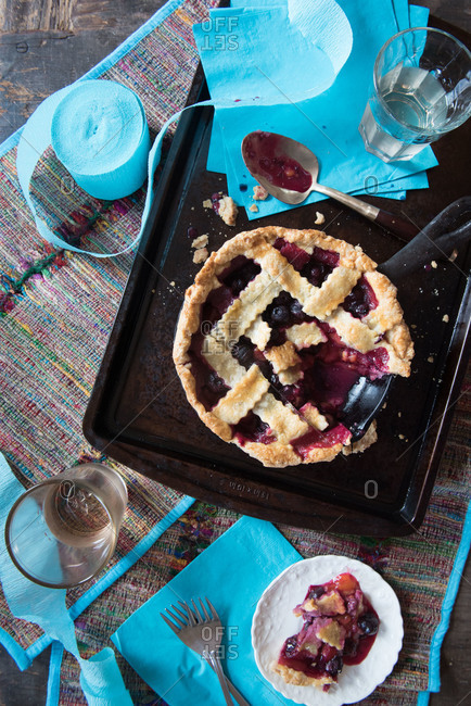 Blueberry plum pie with slice on a plate
