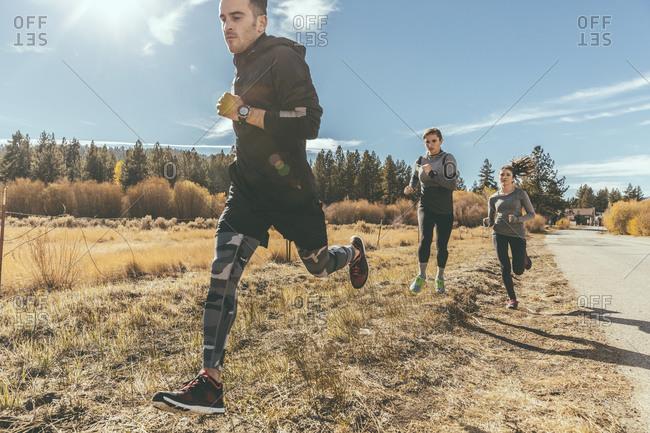 Three people jogging along rural road