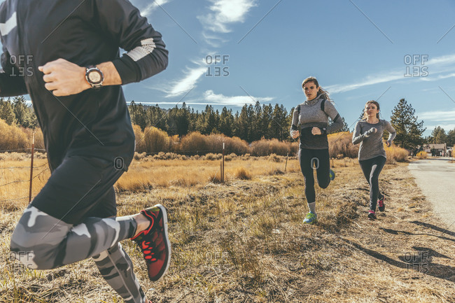 Three people jogging along country road