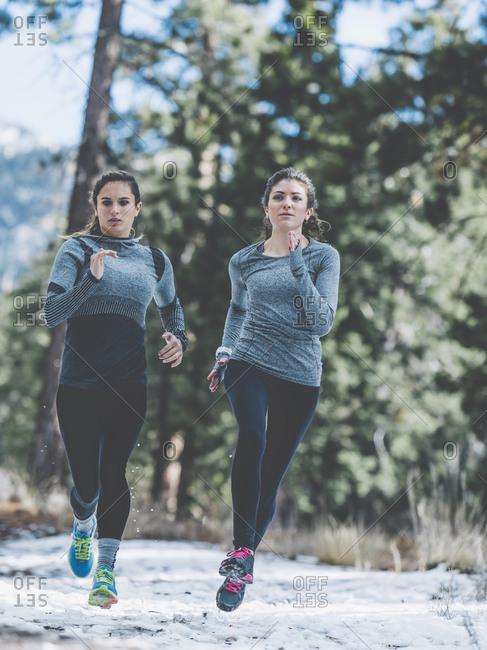 Two women jogging in snowy clearing