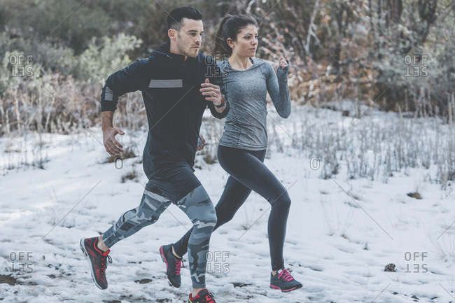 Two people jogging together in snowy countryside