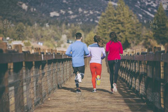 Three people jogging on rural walkway