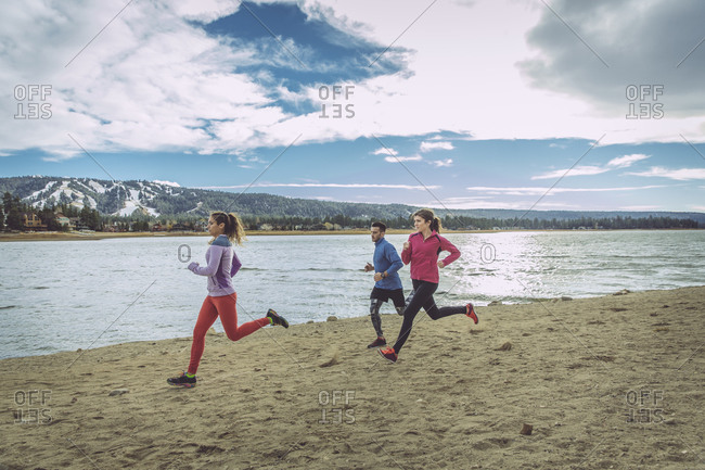 Three people jogging on lake beach