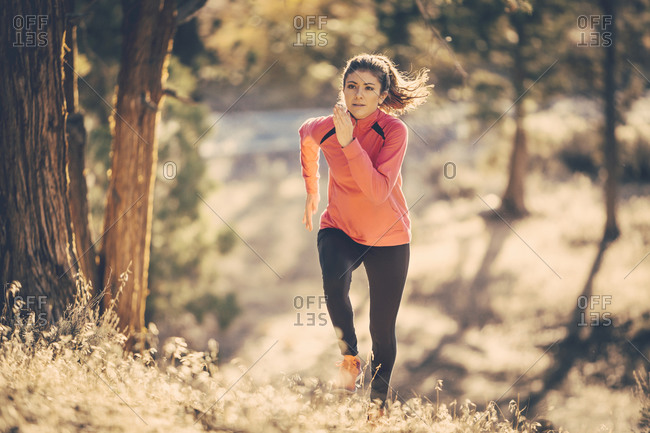 Woman running up hill in woods