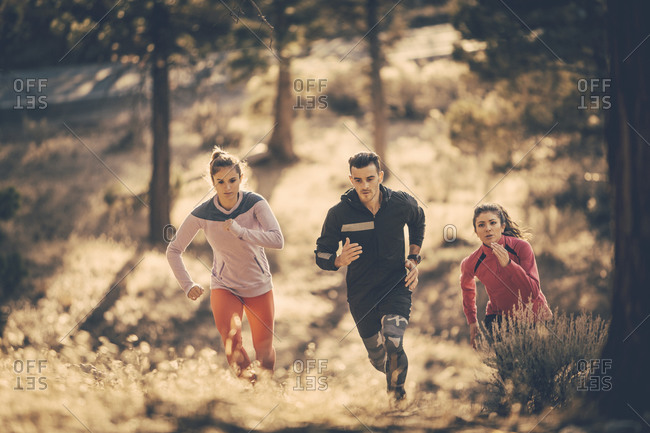 Three people running up hill in woods