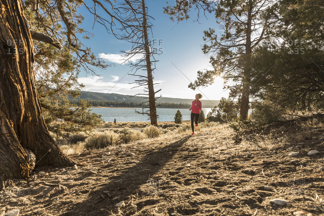 Woman running along lake shore wilderness