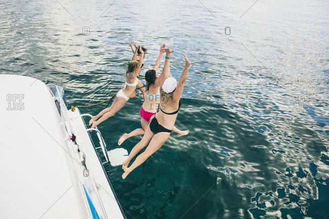 Four women jumping off boat into sea