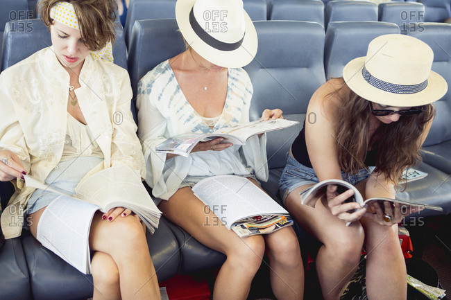 Three women reading magazines in airport
