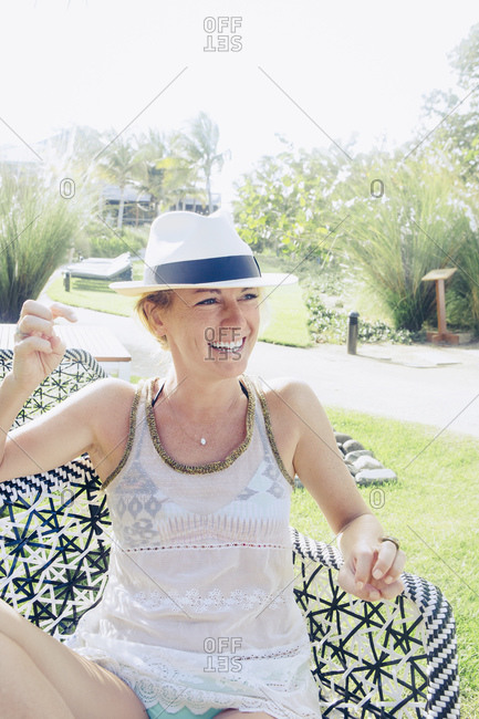 Woman in tropical setting sitting and smiling