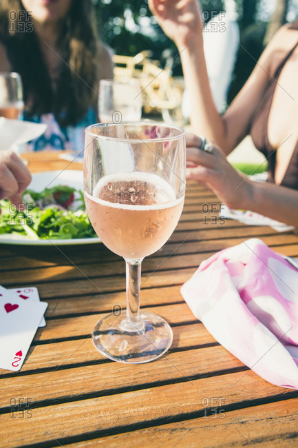 Glass of sparkling wine on table shared by friends