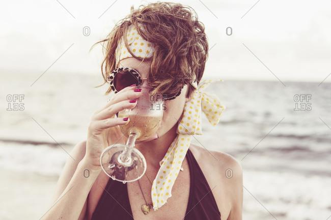 Woman sitting on beach drinking sparkling wine