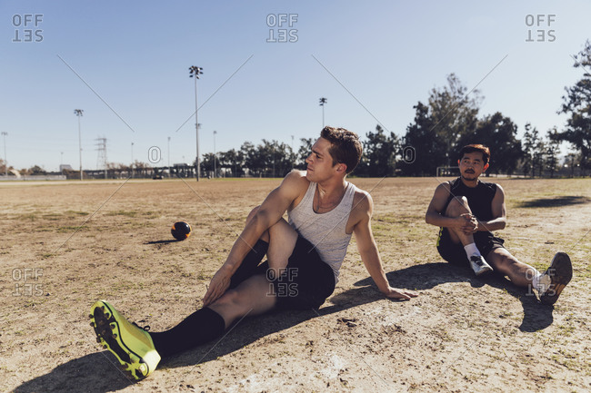 Two men stretching in a soccer field